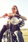 Young girl sitting on vintage custom motorcycle and drinking juice . Outdoor lifestyle portrait. Young girl sitting on vintage custom motorcycle and drinking stock image