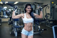 Young sexy girl in a sports gym. Shorts and T-shirt for sports Stock Photo