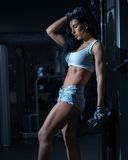 Young sexy girl in a sports gym. Shorts and T-shirt for sports Stock Photography