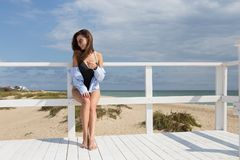 Young sexy girl standing on piece of white wood on a beach wearing black swimwear, blue shirt and sunglasses. There are sea and. Young sexy girl standing on a Stock Photo