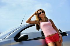 Young sexy girl with sunglasses leaning on cabrio  Royalty Free Stock Photo