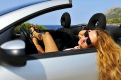 Young sexy girl with sunglasses lying on cabrio sp Royalty Free Stock Image