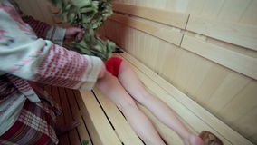 Young sexy girl sweating in the in wooden sauna. Lady hover brooms. stock video