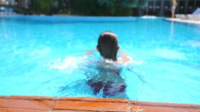 Young sexy girl swimming across pool of luxury hotel. Attractive tanned woman refreshing in basin during summer travel