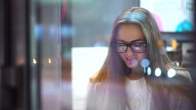 Young sexy girl using tablet in cafe in evening in city, smilling. 4k. Beautiful woman using tablet computer touchscreen in cafe. 4k stock footage