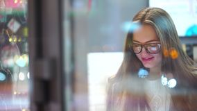 Beautiful woman in glasses using tablet computer touchscreen in cafe in the evening in city. 4k. Young sexy girl using tablet in cafe, smilling. 4k stock video footage