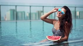 Young sexy girl with watermelon slice in pool stock video footage