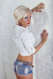 Young sexy girl in white jacket  and blue jeans Stock Photos