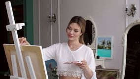 A young sexy girl in a white shirt draws on canvas at home in the bedroom. Art. A young sexy girl in a white shirt draws on canvas at home in the bedroom among stock footage