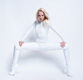 Young sexy girl in white suit. Young female contortionist in glossy vinyl suit looking straight Royalty Free Stock Images