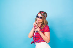 Young sexy hipster woman drinking tasty smoothie, vintage outfit, make up sunglasses, studio lifestyle portrait, dessert Royalty Free Stock Photos