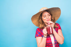 Young sexy woman drinking tasty smoothie on blue background and copy space, vintage outfit, studio lifestyle portrait Stock Images