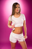 Young Sexy Lady in White Pose with Small Barbells. Pretty Young Sexy Lady in White Sports Attire, Pose with Light Weight Barbells. Isolated on Violet Stock Photography