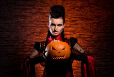 A young and sexy ledy vampire holding a pupmpkin Stock Images