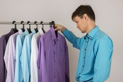 Young sexy man chooses a shirt from a variety of shirts hanging. Young handsome sexy man chooses a shirt from a variety of shirts hanging on hangers on a white Stock Images