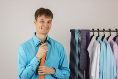 Young sexy man chooses a shirt from a variety of shirts hanging. Young handsome sexy man chooses a shirt from a variety of shirts hanging on hangers on a white Royalty Free Stock Photos