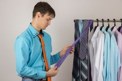 Young sexy man chooses a shirt from a variety of shirts hanging. Young handsome sexy man chooses a shirt from a variety of shirts hanging on hangers on a white Royalty Free Stock Images
