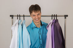 Young man chooses a shirt from a variety of shirts hanging Royalty Free Stock Image