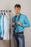 Young man chooses a shirt from a variety of shirts hanging Royalty Free Stock Photos