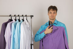 Young sexy man chooses a shirt from a variety of shirts hanging Royalty Free Stock Images
