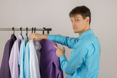 Young sexy man chooses a shirt from a variety of shirts hanging Stock Photos