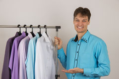 Young sexy man chooses a shirt from a variety of shirts hanging Stock Images