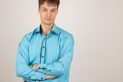 Young sexy man chooses a shirt from a variety of shirts hanging. Young handsome sexy man chooses a shirt from a variety of shirts hanging on hangers on a white Stock Image