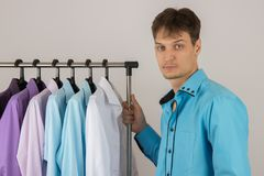 Young sexy man chooses a shirt from a variety of shirts hanging. Young handsome sexy man chooses a shirt from a variety of shirts hanging on hangers on a white Royalty Free Stock Photo