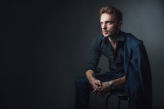 Young sexy man in a classic suit sitting on a chair. Portrait of a young sexy man in a classic suit. A man sitting in a relaxed position. A man wearing a black Stock Photography