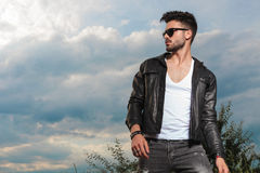 Young man in leather jacket and sunglasses standing outdoor royalty free stock photos