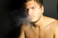 Young Sexy Man Smoking a cigarette Stock Images
