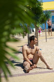 Young sexy man on a tropical resort. Sitting about palm tree Royalty Free Stock Photography