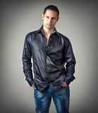 Young sexy man wearing black shirt. Fashion portrait of young sexy man wearing black shirt  poses on gray background in studio Royalty Free Stock Images