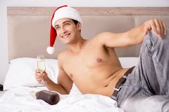 The young man wearing santa hat in bed Stock Image
