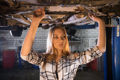 Young mechanic woman standing under the car in car repair service. Looking to the side. Mid shot stock photos