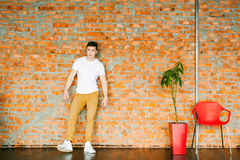Young men bodybuilder athlete,studio portrait in loft, guy model in white T-shirt and brown trousers. Young man bodybuilder athlete,studio portrait in loft, guy royalty free stock photos