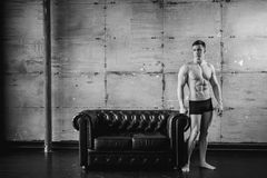 Young sexy men bodybuilder athlete, Studio portrait. Young sexy man bodybuilder athlete stands at black leather couch with a naked torso, studio portrait Royalty Free Stock Photography