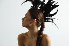 Young sexy mixed race caucasian woman vogue portrait with feather mohawk accessory wearing black bodysuit. Young sexy mixed race caucasian woman vogue portrait Stock Photos