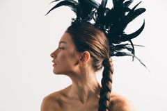 Young mixed race caucasian woman vogue portrait with feather mohawk accessory wearing black bodysuit. stock image