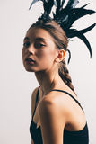 Young mixed race caucasian woman vogue portrait with feather mohawk accessory wearing black bodysuit. stock images