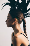 Young mixed race caucasian woman vogue portrait with feather mohawk accessory wearing black bodysuit. royalty free stock images