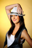 Young sexy model in jeans and white hat. Yellow background Stock Image