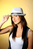 Young sexy model in jeans and white hat. Yellow background Royalty Free Stock Images