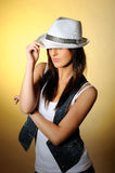 Young sexy model in jeans and white hat. Yellow background Royalty Free Stock Photo