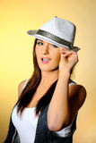 Young sexy model in jeans and white hat. Yellow background Stock Photo
