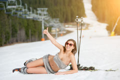 Young sexy naked skier is lying on snowy slope under ski lift at ski resort Royalty Free Stock Image