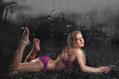 Young sexy nude woman posed wet. Water studio photo. Royalty Free Stock Photo