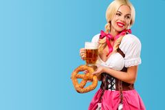 Free Young Sexy Oktoberfest Girl - Waitress, Wearing A Traditional Bavarian Dress, Serving Big Beer Mugs On Blue Background Stock Photo - 100982840