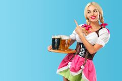 Young sexy Oktoberfest girl - waitress, wearing a traditional Bavarian dress, serving big beer mugs on blue background Stock Photography