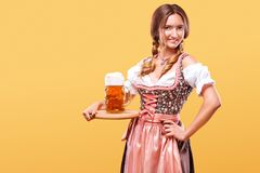 Young sexy Oktoberfest girl - waitress, wearing a traditional Bavarian dress, serving big beer mugs on orange background Stock Images